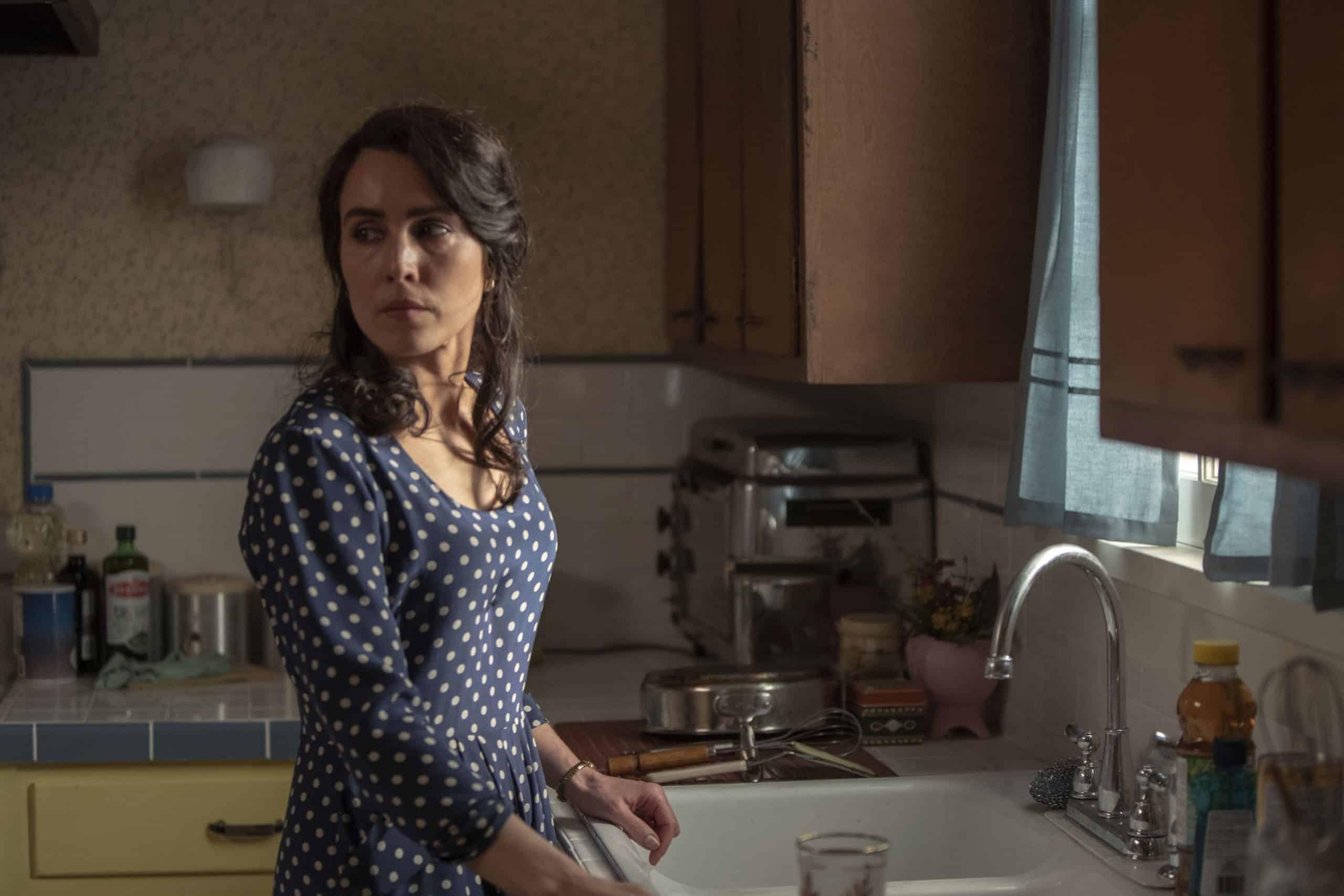 Noomi Rapace ist misstrauisch ihrem Mann gegenüber und beäugt diesen aus der Küche. The Secrets we keep ist ein neuer Thriller mit Noomi Rapace