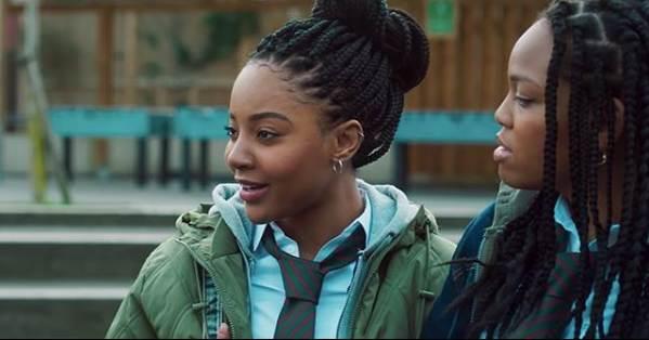 Filmszene aus Blue Story. Zwei Freundinnen auf dem Schulhof in London.