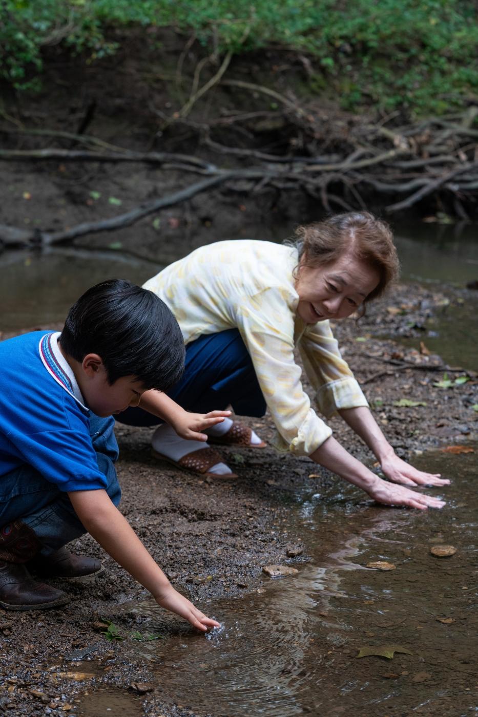 David (Alan S. Kim) und seine Großmutter Soonja (Youn Yuh-Jung) suchen gemeinsam nach einem Ort, wo die Minari-Pflanze gedeihen kann.