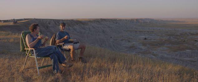 Frances McDormand und David Strathairn in NOMADLAND sitzen auf Campingstühlen im Nirgendwo.