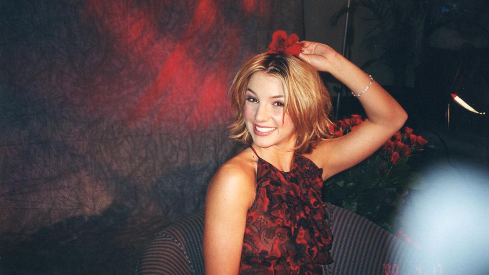 Britney Spears in einem roten Kleid mit deiner Hand hält sie lächelnd eine Rose auf ihrem Kopf