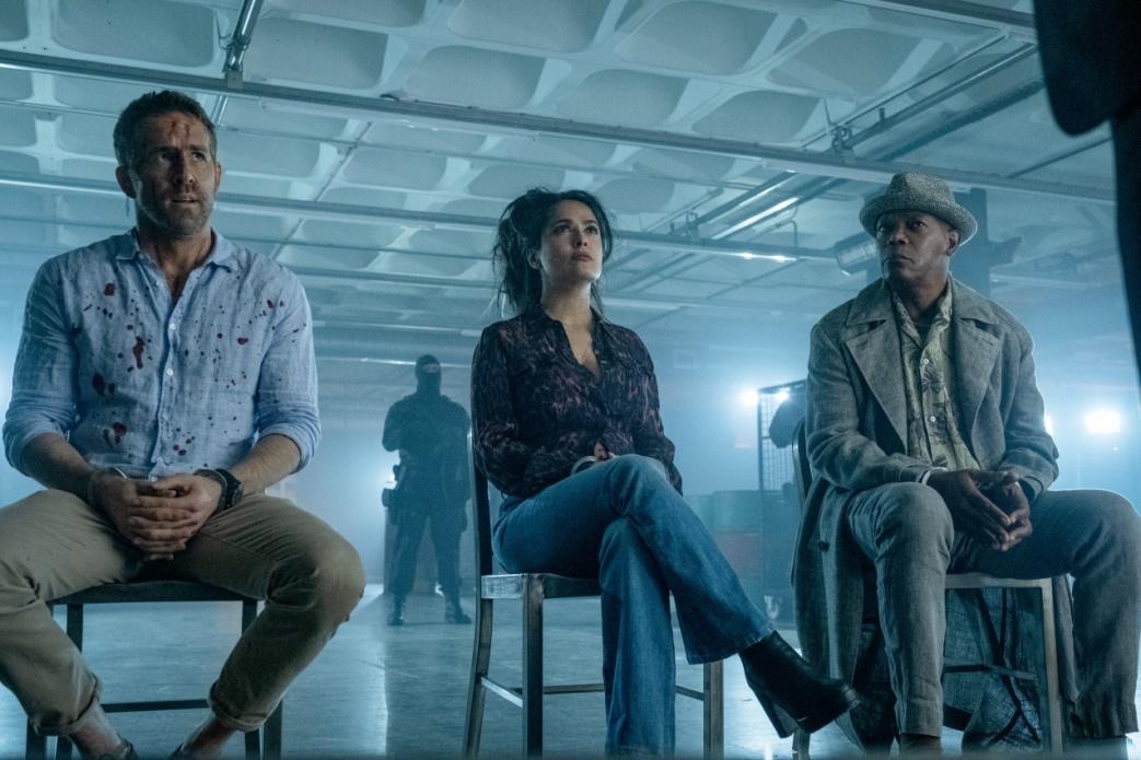Ryan Reynolds, Selma Hayek und Samuel L.Jackson sitzend auf Stühlen nebeneinander, im Film Killers Bodyguard 2.