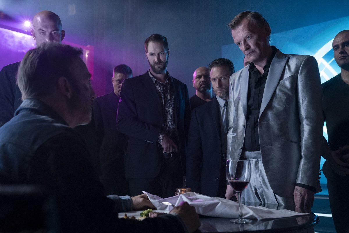 Hutch Mansell (Bob Odenkirk, sitzend mit dem Rücken zur Kamera), Albert (Neil Davison, vierter von links), Yulian Kuznetsov (Alexey Serebryakov, direkt von Odenkirk stehend) mit weiteren Mitgliedern der russischen Mafia in Nobody,