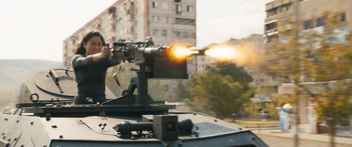 Mit einem Machinengewehr Aufsatz auf einem gepanzerten Fahrzeug, schießt sich eine Frau den Weg in Budapest frei