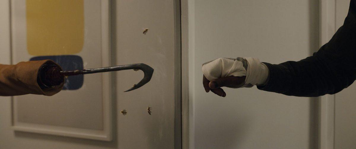 Anthony McCoy (Yahya Abdul-Mateen II, right) streckt seinen Arm in Richtung einer Spiegelreflexion von Candyman aus