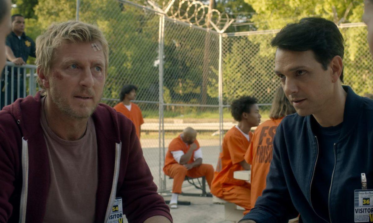 Ralph Macchio u William Zapka sitzen an einem Tisch mit Gefängnisinsassen. Szene aus der Serie Cobra Kai auf Netflix