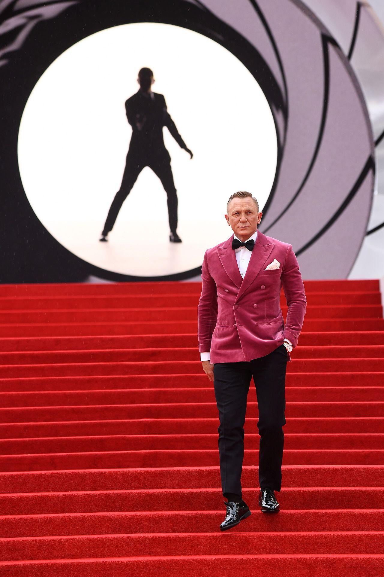 """Daniel Craig besucht die Weltpremiere von """" KEINE ZEIT ZU STERBEN """" schreitet die rote Treppe herunter. im Hintergrund das james Bond Film Eröffnungs Logo"""