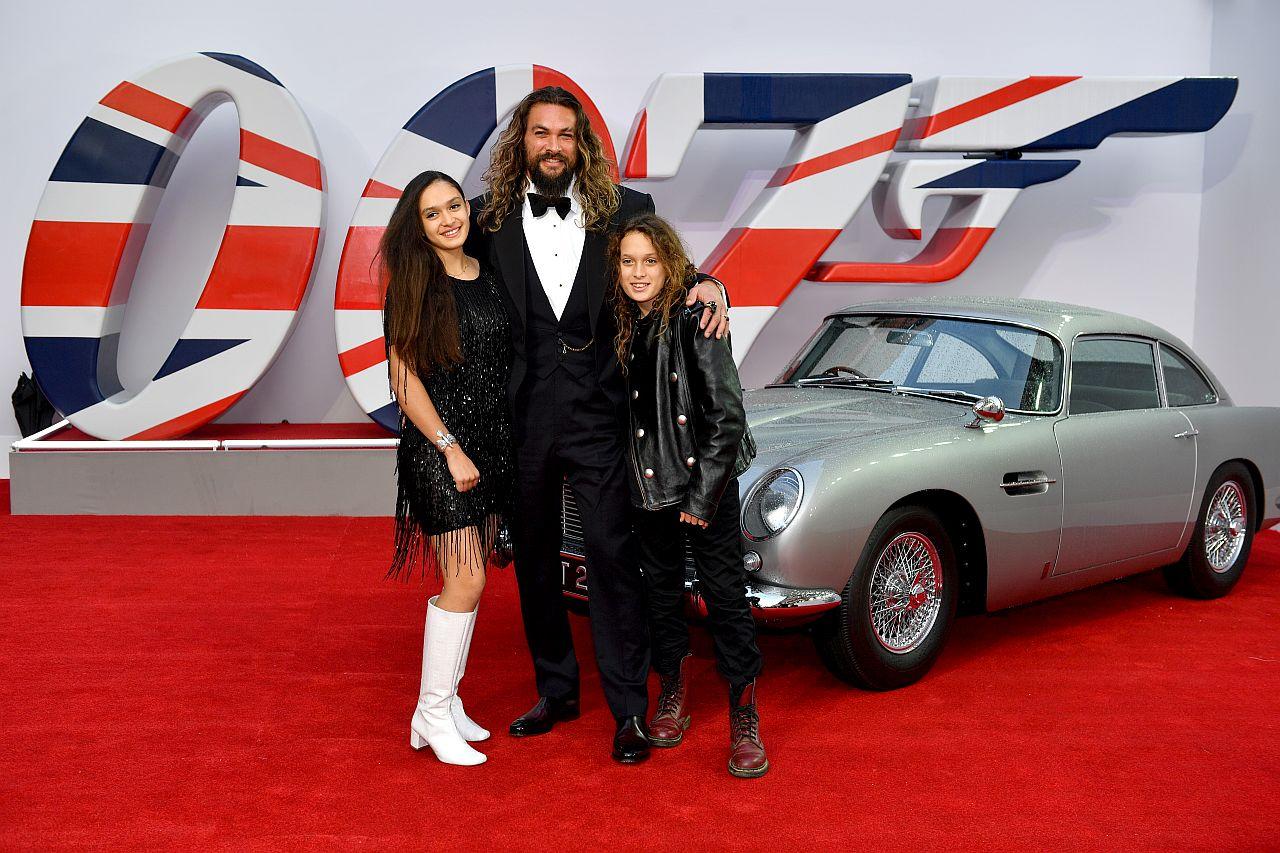 """Lola Iolani Momoa, Jason Momoa und Nakoa-Wolf Manakauapo Namakaeha Momoa stehen neben dem Aston Martin von James Bond bei der Weltpremiere von """" KEINE ZEIT ZU STERBEN"""""""