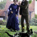 Claire Foy und Benedict Cumberbatch beobachten eine Katze unter einem Regenschirm