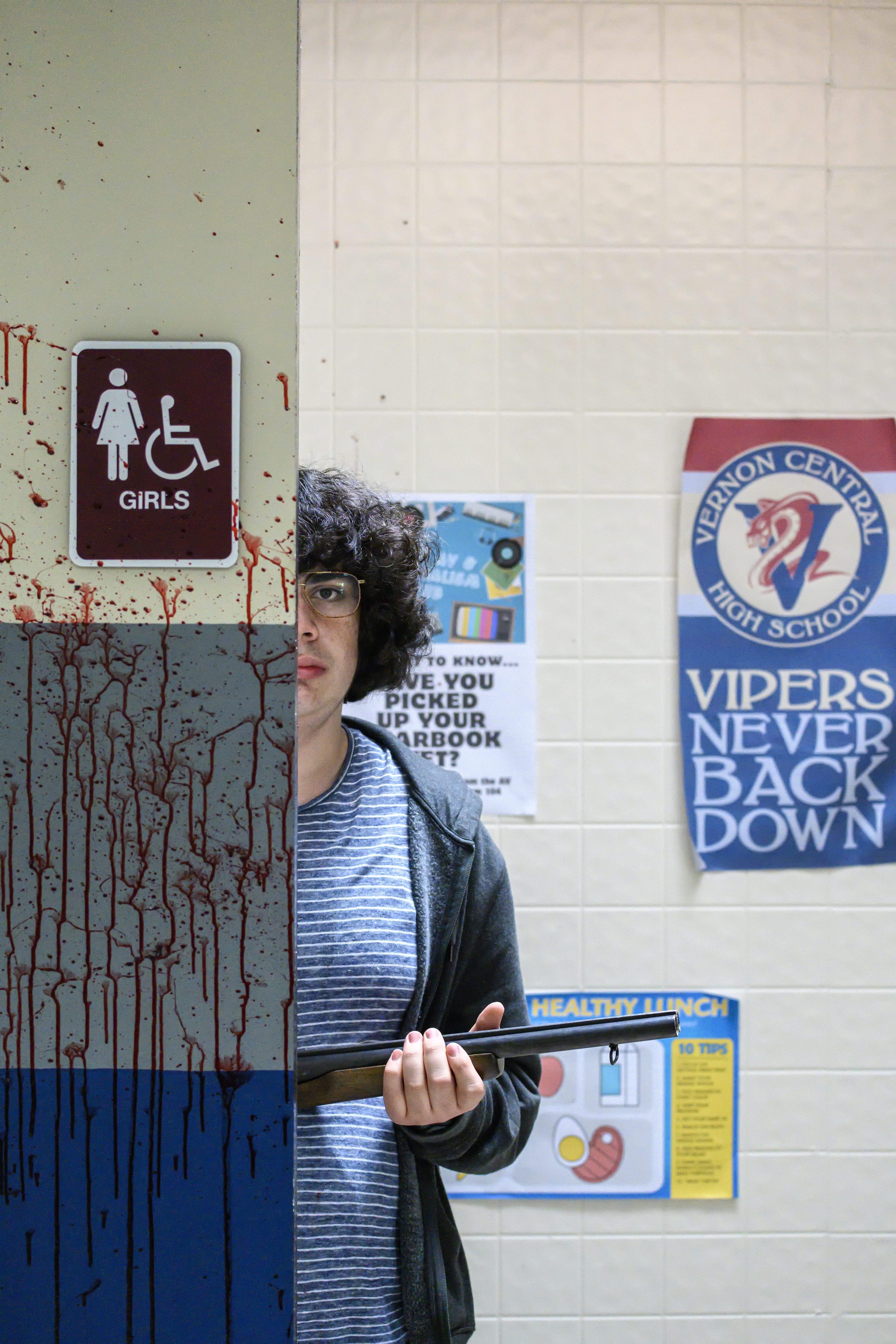 Ein Junge mit einer Waffe schaut hinter der Wand hervor. Er befindet sich auf dem Flur einer Schule. Aus dem film Run Hide Fight