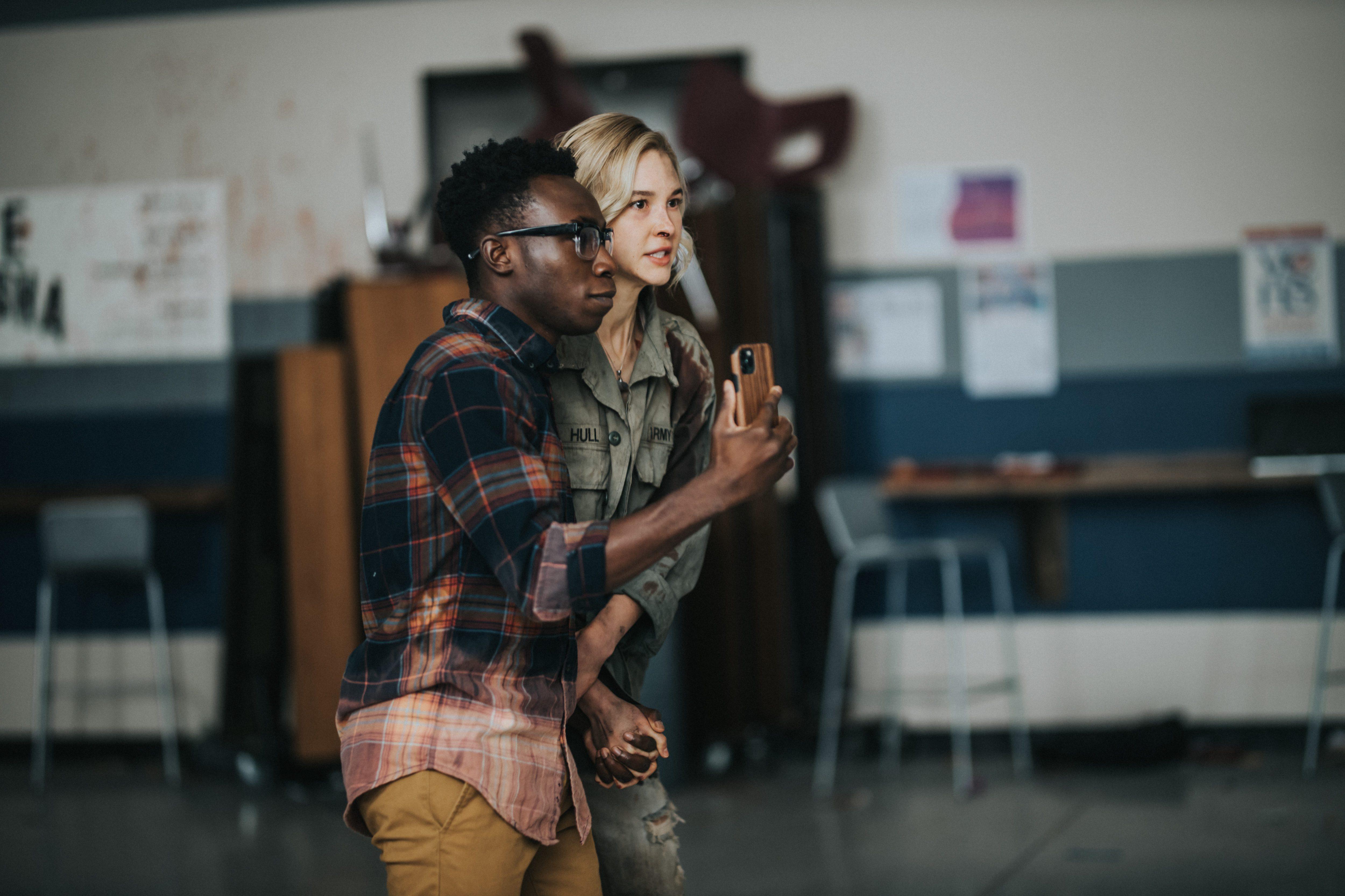 Zwei Jugendliche Hand in Hand in einem Klassenraum. Der Junge hat ein Smartphone ein der Hand